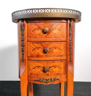 Comodino a tre cassetti in stile Luigi XV a sezione ovale, in legno impiallacciato e intarsiato in varie essenze, fregi in metallo. Novecento