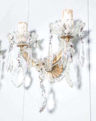 Coppia di appliques Maria Teresa in cristallo di Boemia a due luci. Primo Novecento. Nel 1743, in onore dell'imperatrice austriaca Maria Teresa (1717-1780), fu realizzato un lampadario che divenne il prototipo di un intero genere: si tratta di un lampadario a sospensione con telaio in metallo in cui il corpo dorato è impreziosito al centro da un fusto ornamentale in vetro. Di grande effetto, i bracci sono sporgenti e decorati con elementi a forma di goccia realizzati in cristallo di Boemia.