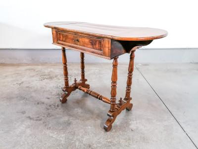 Tavolino da lavoro a bandelle laterali in legno di noce e radica di noce, in parte massello e in parte impiallacciato, con cassetto frontale. Fine Ottocento