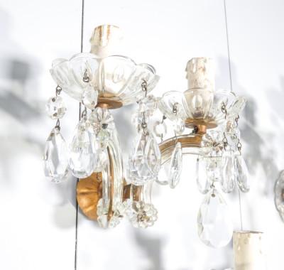 Tris di appliques Maria Teresa in cristallo di Boemia a due luci. Primo Novecento. Nel 1743, in onore dell'imperatrice austriaca Maria Teresa (1717-1780), fu realizzato un lampadario che divenne il prototipo di un intero genere: si tratta di un lampadario a sospensione con telaio in metallo in cui il corpo dorato è impreziosito al centro da un fusto ornamentale in vetro. Di grande effetto, i bracci sono sporgenti e decorati con elementi a forma di goccia realizzati in cristallo di Boemia.