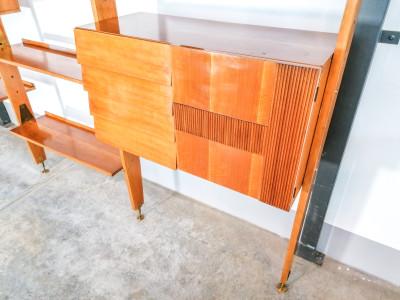 Wall Unit modulare con fissaggio a pavimento e soffitto. Il mobile è composto da 8 ripiani e due armadietti con ante, ripiani (di cui uno in vetro) e cassettini. Viene fissato al soffitto e al pavimento mediante piedini girevoli in ottone, per cui può essere collocato in qualsiasi posizione all