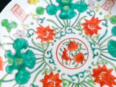 Piattino in porcellana dipinta in policromia con motivi floreali e ideogrammi. Marchio sul retro. Cina, Novecento