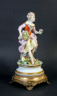 Scultura in ceramica dipinta a mano, manifattura CP Capodimonte. Donna con fiori. Italia, Novecento